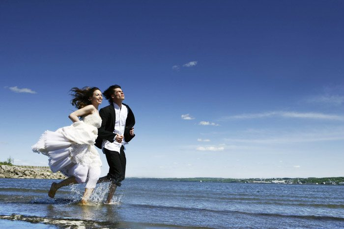 married couple running along the beach